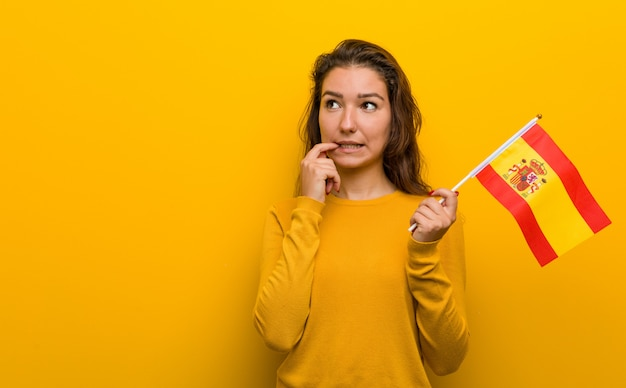 Young european woman holding a spanish flag relaxed thinking about something looking at a copy space.