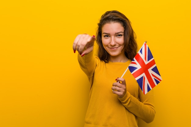 Young european woman holding an united kingdom flag cheerful smiles pointing to front.