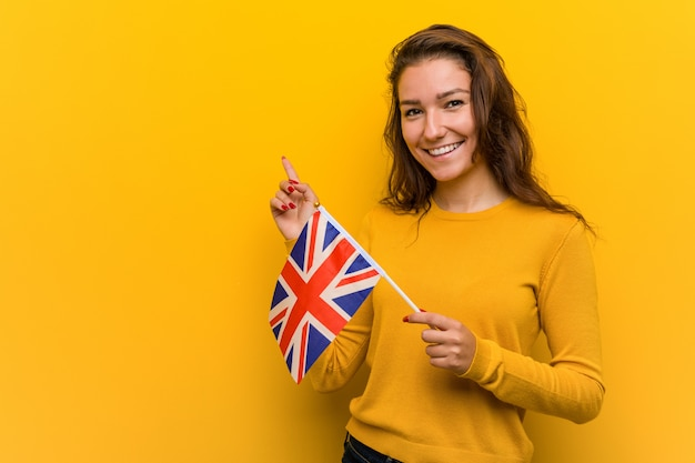 Young european woman holding an united kingdom flag smiling cheerfully pointing with forefinger away