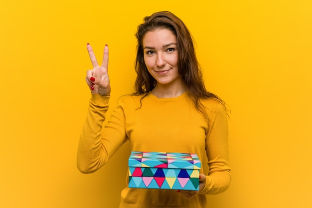 Young european woman holdinggift showing number two with fingers.