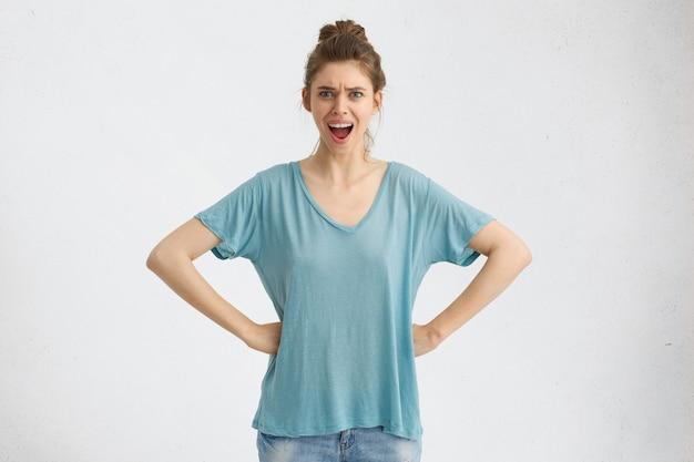 カジュアルな服装の若いヨーロッパ人女性、腰に手をつないで、反抗的な表情で見て、何かに不満を抱いて、怒りで叫んでいます。
