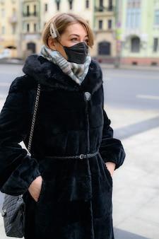 都市の屋外で保護使い捨て医療用黒いマスクの若いヨーロッパの女性。危険な2019-ncovインフルエンザコロナウイルスの概念保護、変異して中国で蔓延。縦の写真