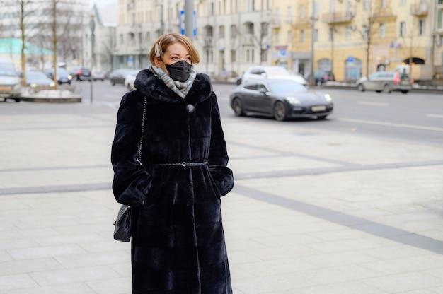 都市の屋外で保護使い捨て医療用ブラックマスクの若いヨーロッパの女性。危険な2019-ncovの概念保護