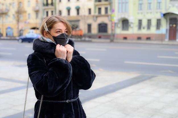 都市の屋外で保護使い捨て医療用ブラックマスクの若いヨーロッパの女性
