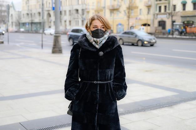 都市の屋外で保護使い捨て医療用ブラックマスクの若いヨーロッパの女性 Premium写真