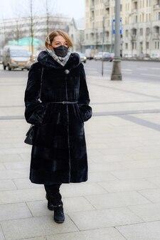 都市の屋外で保護使い捨て医療用ブラックマスクの若いヨーロッパの女性。