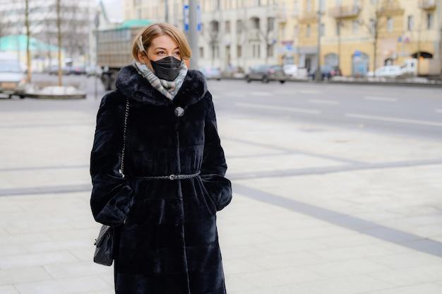 都市の屋外で保護使い捨て医療用ブラックマスクの若いヨーロッパの女性。 Premium写真