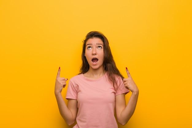 ヨーロッパの若い女性は、空白のスペースを示すことを両手の指で示します。