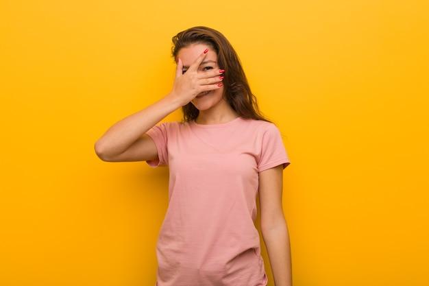 黄色で孤立した若いヨーロッパ人女性は、彼女の指を通して瞬きし、恥ずかしそうに顔をなでた。