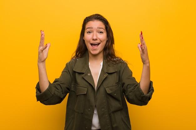 黄色で孤立した若いヨーロッパの女性は、嬉しい驚きを受け取り、興奮し、手を上げます。