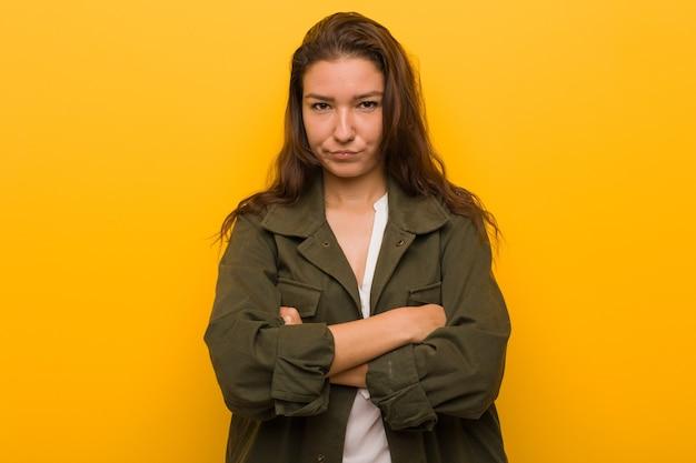 Молодая европейская женщина, изолированная над желтым, недовольно нахмурившись, скрестила руки.