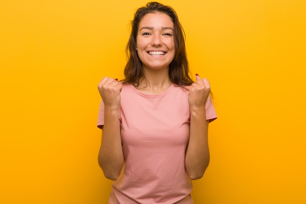 Young european woman isolated over yellow background cheering carefree and excited. victory concept.