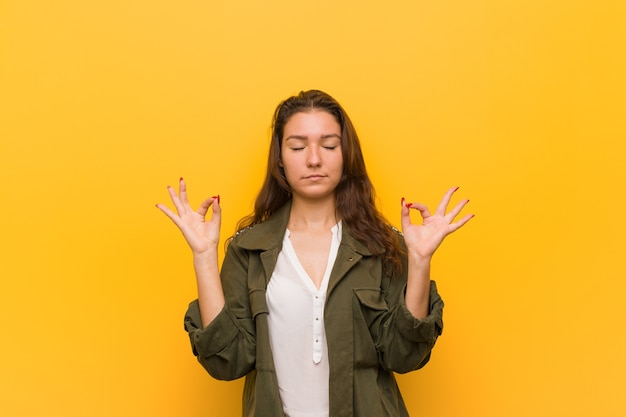 Young european woman isolated over yellow background relaxes after hard working day, she is performing yoga.