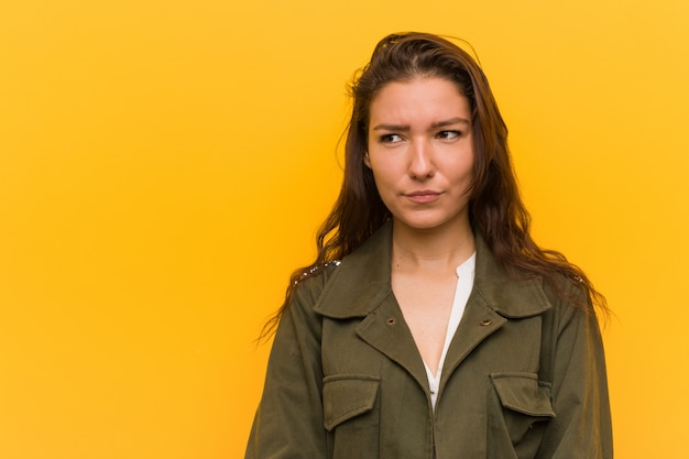 Young european woman isolated over yellow confused, feels doubtful and unsure.