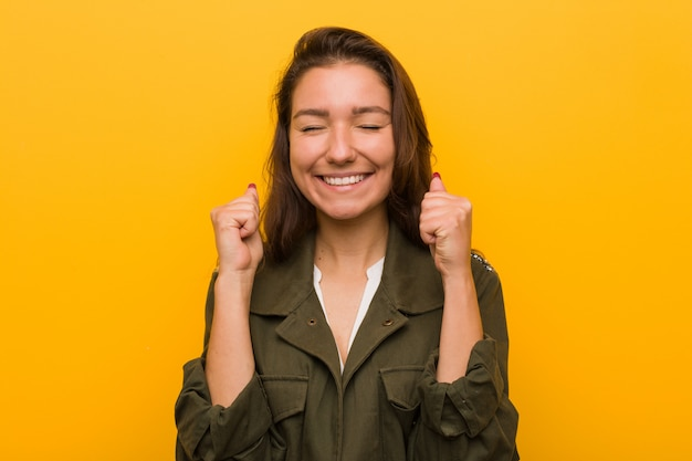 Young european woman isolated over yellow raising fist, feeling happy and successful.