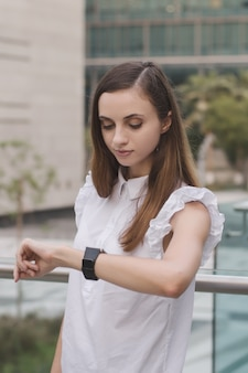 Young european woman looking at her hand watches