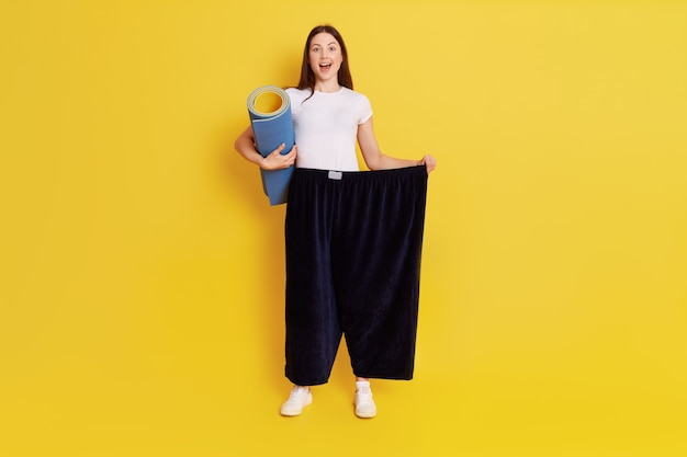 Young european woman in oversize black pants posing isolated over yellow wall, holding karemat in hands for doing sports, has excited facial expression, rejoices at achieved result.