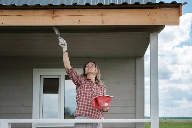 새로운 목조 주택의 베란다 그림 젊은 유럽 여자