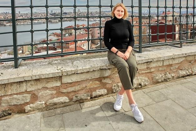 Молодая европейская женщина позирует на фоне городского пейзажа во время прогулки по стамбулу.