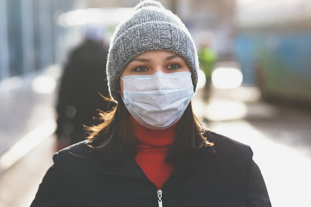 Young european woman in protective disposable medical mask on the city street. concept protection of dangerous 2019-ncov influenza coronavirus