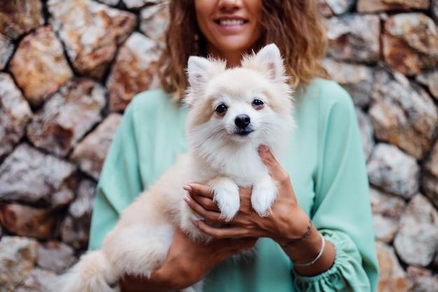 Young european woman in romantic summer dress bracelet holds cute fluffy pomeranian puppy spitz outside villa