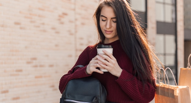 Young european woman sit with coffee cup asmartphone and shopping bags
