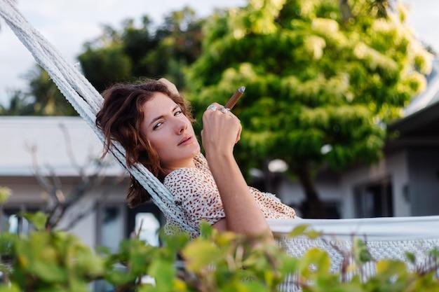 Sigaro di fumo della giovane donna europea sdraiato sull'amaca fuori dall'hotel villa di lusso tropicale, luce naturale al tramonto