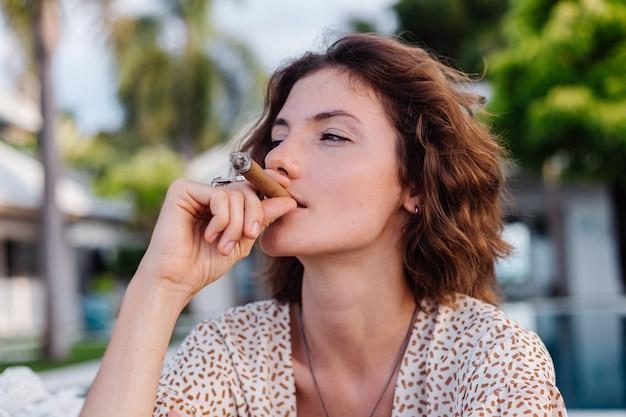 Young european woman smoking cigar lying on hammock outside tropical luxury villa hotel, sunset natural light