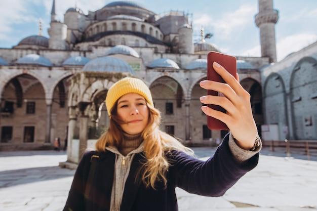 Молодая европейская женщина принимает портрет selfie в стамбуле, турции. девушка гуляет по зимнему стамбулу. блондинка фотографирует телефон на фоне мечети в осенний день.