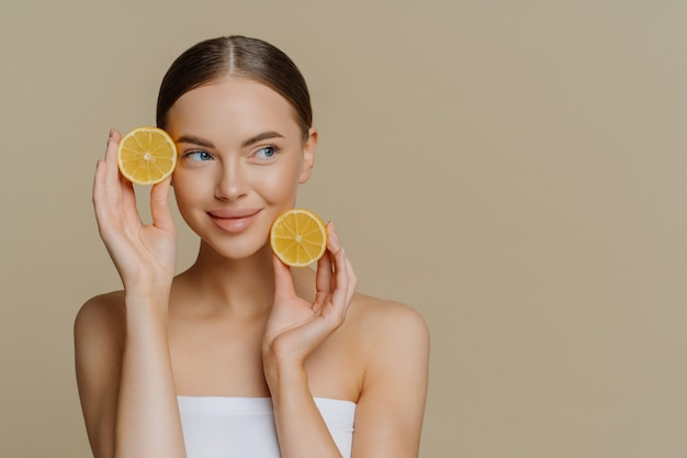 Young european woman uses homemade fruit for facial mask holds lemon slices