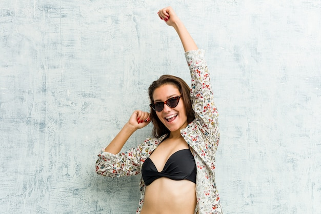 Young european woman wearing bikini celebrating a special day, jumps and raise her arms with energy.