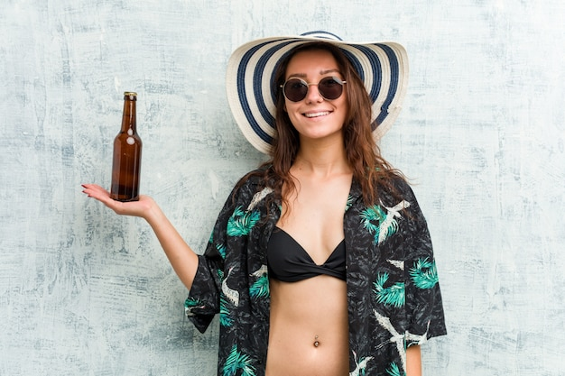 Young european woman wearing bikini and drinking a beer
