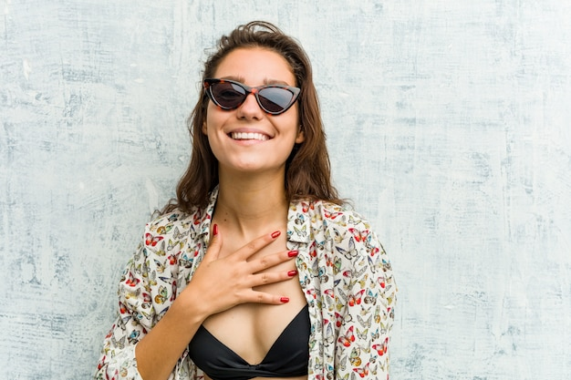 Young european woman wearing bikini laughs out loudly keeping hand on chest.