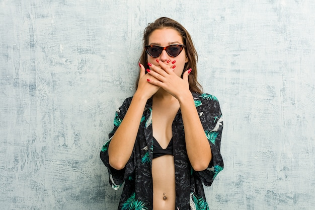 Young european woman wearing bikini shocked covering mouth with hands.