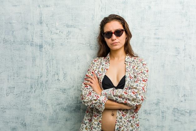皮肉な表情に不満を持ってビキニを着ている若いヨーロッパの女性。
