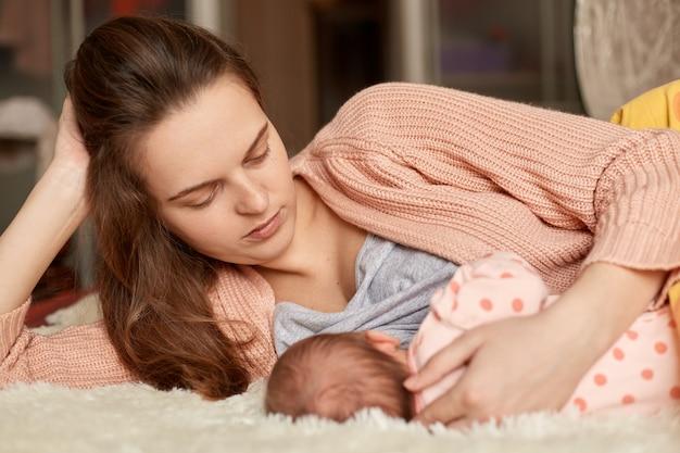 그녀의 새로 태어난 아기와 함께 침대에 누워 집에서 옷을 입고 젊은 유럽 여성, 유아 및 먹이, 작은 아이 식사, 모유 수유, 집에서 아이와 엄마를보고.