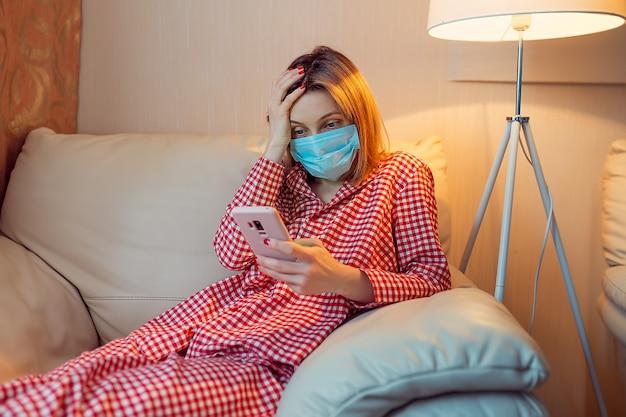 Молодая европейка в хирургической маске остается дома во время вспышки коронавируса, коронавируса и смотрит новости или приложение на смартфоне