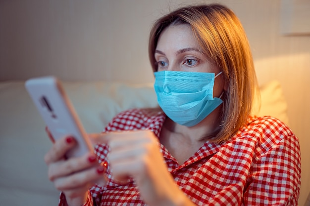 手術用フェイスマスクを身に着けている若いヨーロッパの女性は家にいる