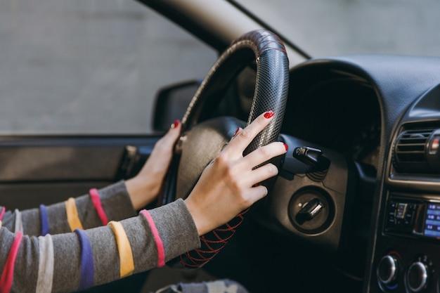 Una giovane donna europea con una pelle sana e pulita ha messo le mani con una manicure rossa sulle unghie sul volante dell'auto con interni neri. concetto di viaggio e di guida.