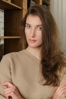 ベージュのジャンパーで長い髪の若いヨーロッパの女性