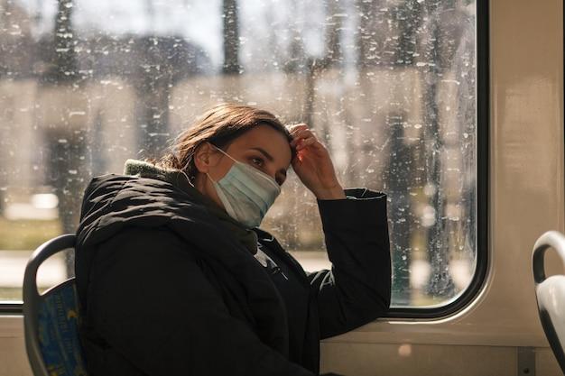 Молодая европейская женщина с медицинской маской в городском транспорте