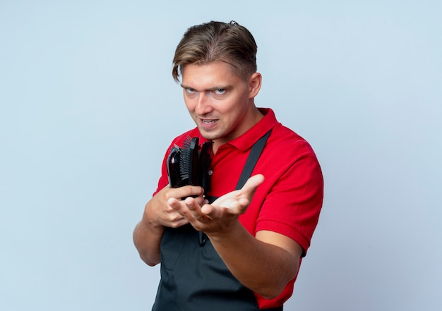 Young evil joyful blonde male barber in uniform holds barber tools holding hand out