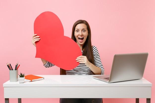 パステルピンクの背景で隔離のpcラップトップで白い机に座って、赤い空の空白の心を保持している若い興奮した驚いた女性。業績ビジネスキャリアコンセプト。広告用のスペースをコピーします。