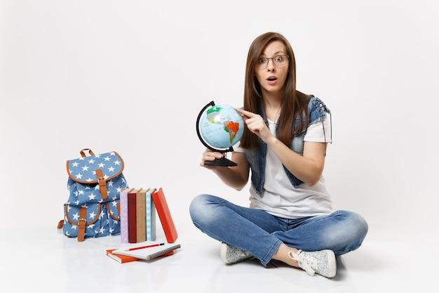 Giovane studentessa stupita eccitata che tiene il globo puntando il dito indice sul paese, posto seduto vicino allo zaino, libri scolastici isolati