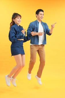 Молодые взволнованные азиатские люди мужчина и женщина прыгают, изолированные на желтом фоне