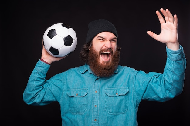 A young excited bearded man is screaming and holding a soccer ball up near a black wall