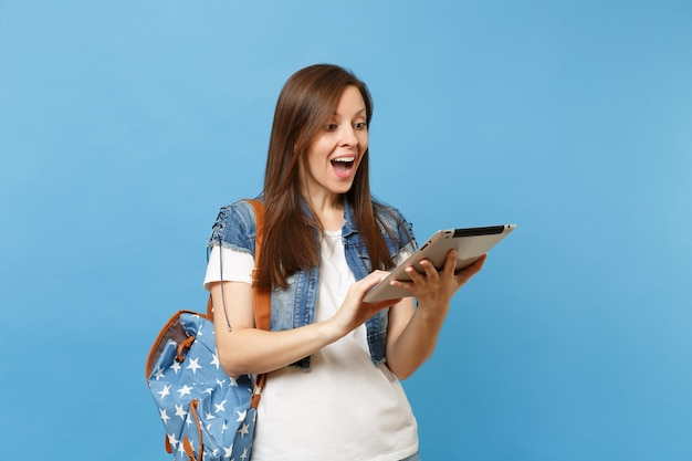 파란색 배경에 격리된 태블릿 pc 컴퓨터 작업을 사용하여 배낭을 들고 입을 벌린 젊은 흥분된 아름다운 여성 학생. 고등학교에서 교육입니다. 광고 공간을 복사합니다.