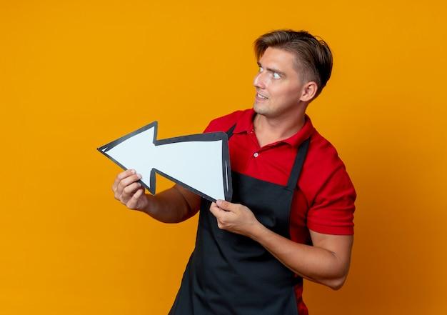 制服を着た若い興奮した金髪の男性理髪師は方向マークを保持し、コピースペースでオレンジ色のスペースに分離された側を見て