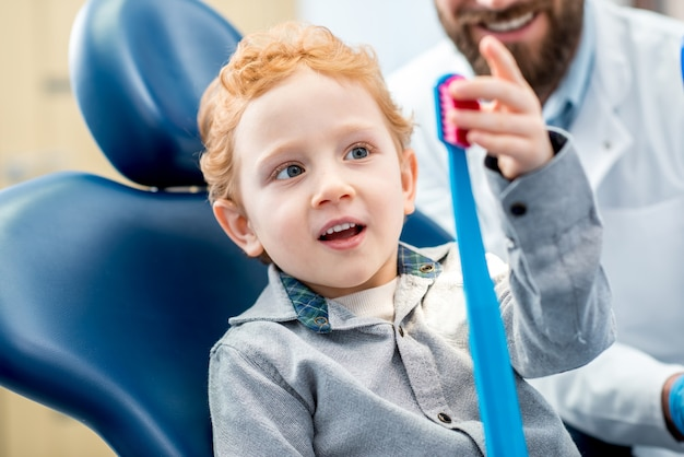 Young excited boy sitting on the chair holding big toothbrush with doctor in the dental office