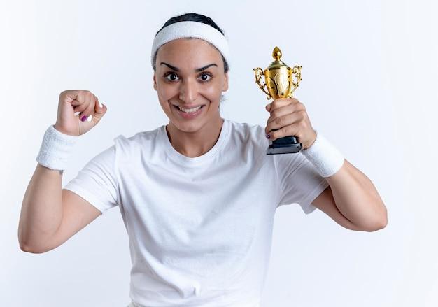 머리띠와 팔찌를 착용하는 젊은 흥분된 백인 스포티 한 여자 우승자 컵을 보유하고 복사 공간이있는 흰색 공간에 고립 된 주먹을 제기